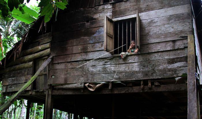 Seorang anak mengintip di jendela rumah kayunya di Desa Seumirah, Nisam Antara, Aceh Utara, Provinsi Aceh | foto Rahmad Antara